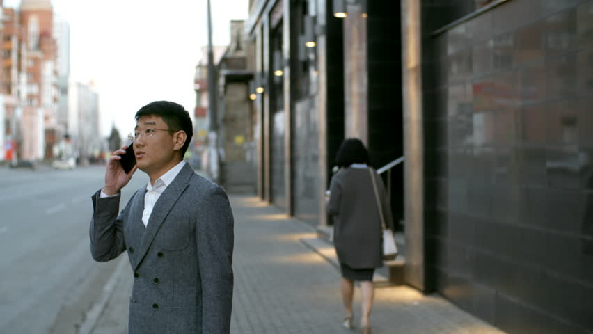 Tilt down shot of Asian man in formal clothes and glasses standing on pavement and discussing work with colleagues on the phone #1020151588
