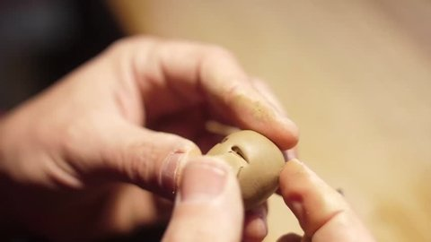 sculpting a small doll head in clay art slow motion