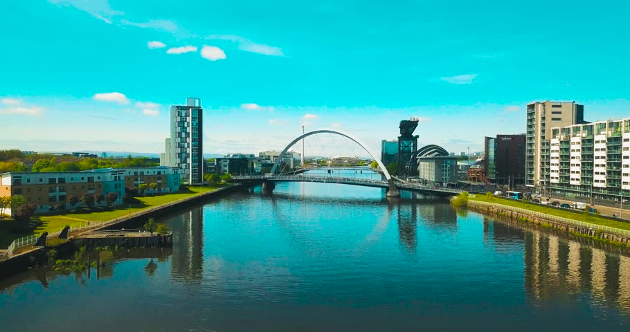 Drone shot of the River Clyde, jibs up to reveal the Clyde Arc (Squinty Bridge) & the cityscape of Glasgow.