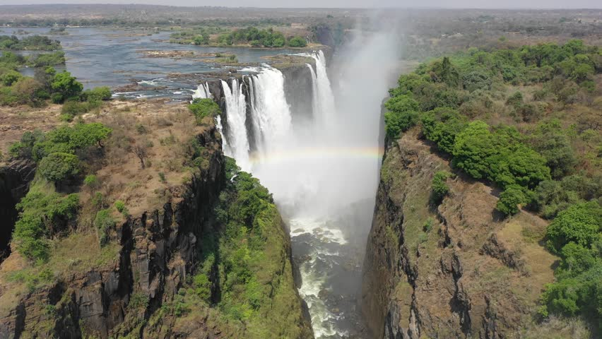 Drone flight at the full length of the world famous Victoria Falls, right at the border between Zambia and Zimbabwe in Southern Africa. The flight starts in Zimbabwe and ends in Zambia.