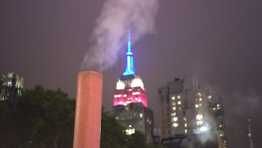 NEW YORK CITY, NY - SEPTEMBER 11 : Steam in street with NYC in background at night New York City, New York on September 11, 2018. | Shutterstock HD Video #1020179953