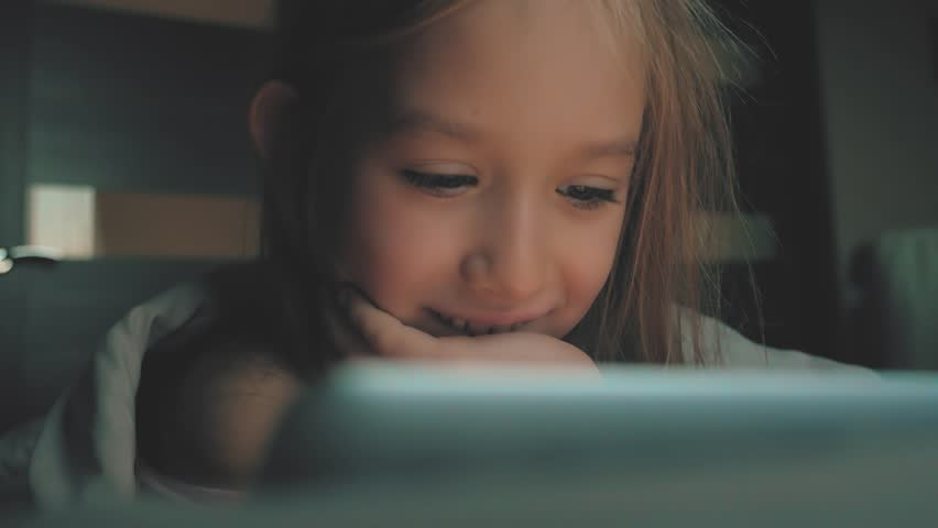 Teenage girl in bed playing a tablet in social internet in the dark light. Close up of little girl watching video on the digital tablet at night.