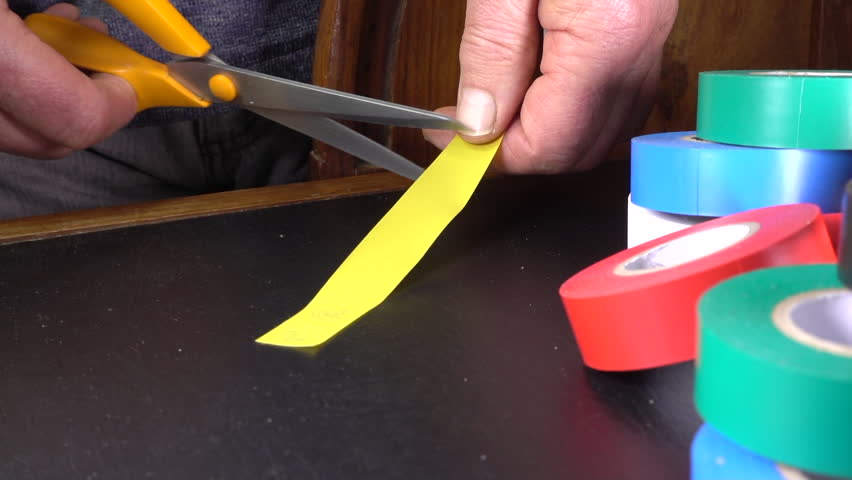 Slow motion close POV shot of a man's hands cutting a piece of yellow electrical tape, with a selection of rolls nearby. Royalty-Free Stock Footage #1020192706