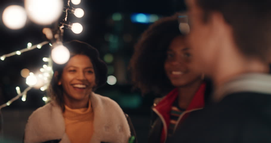 happy group of friends dancing to lively rooftop party music enjoying weekend celebration in urban city at night #1020197446