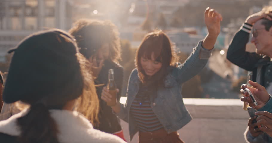 Slow motion group of multiracial friends hanging out young asian woman dancing enjoying rooftop party at sunset drinking alcohol having fun on weekend celebration