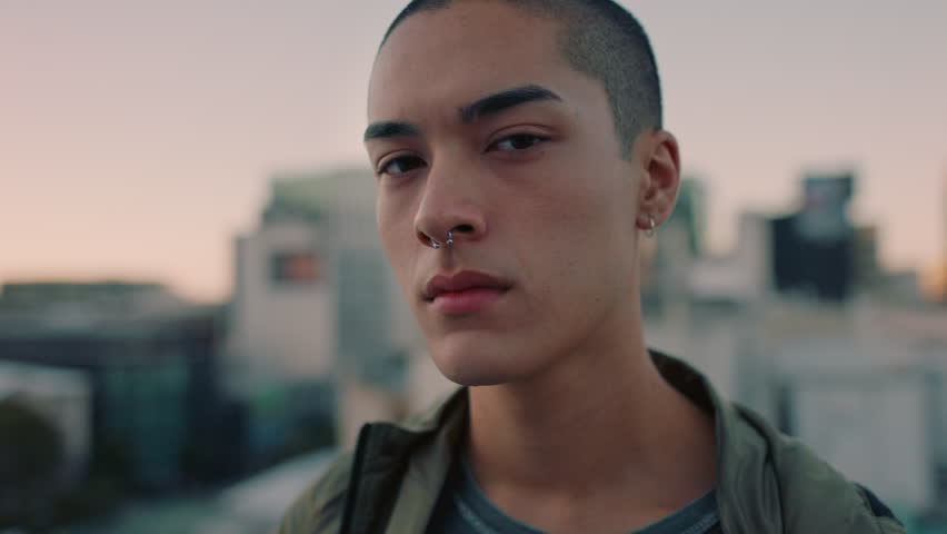 portrait attractive young mixed race man with shaved hair on rooftop at sunset wearing piercings looking confident in urban city background #1020203146