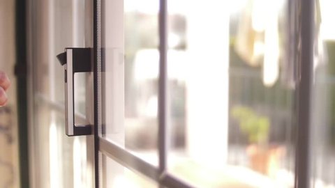 young man opening balcony sliding window door slow motion