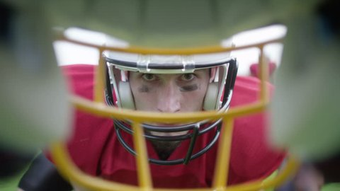 4K Opposing American football players ready to play, as seen through the face mask of one of the players