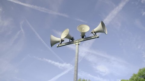 Outdoor public address loudspeakers against a blue sky and trees in slow motion