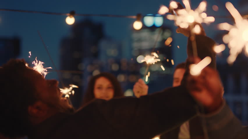 Cheerful group of friends holding sparklers celebrating new years eve on rooftop at night having fun dancing enjoying holiday party celebration diverse young people waving festive fireworks