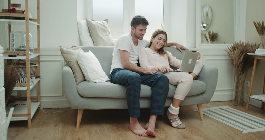 Capturing one couple in the morning have a nice time together in living room with cozy style, they are looking through the notebook have a good mood. | Shutterstock HD Video #1020254320
