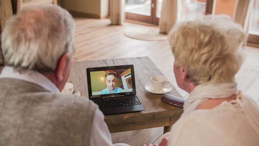Boy waving over video call with grandparents HD. Over shoulder view of elderly couple calling grandson with video call on laptop computer. Laptop on wooden desk. Two person sit on sofa. | Shutterstock HD Video #1020255901