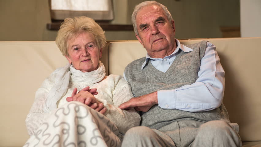 Elderly couple on sofa caressing looking of camera HD. Old married grandparents enjoying time together at home on sofa sitting together, grandma caressing husband hand. Retro clothes.