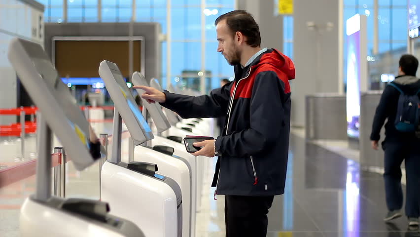Passenger Checking In At Airport With Kiosk And Printing Boarding Pass