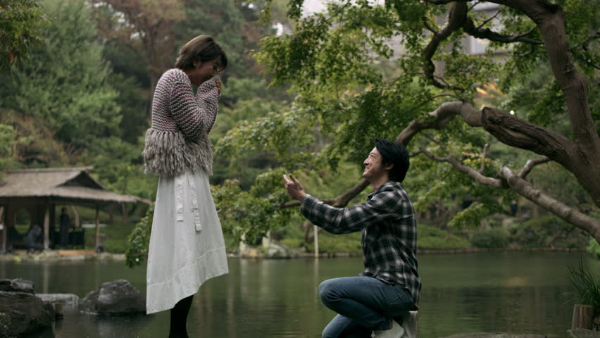 Cheerful Japanese man proposes to his girlfriend and they hug happily in a beautiful garden. Romantic proposal scene. Wide shot on 4k RED camera.