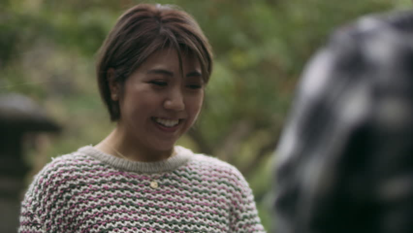 Surprised Japanese woman sees her boyfriend proposing to her with a ring and accepts happily and hugs him in a beautiful garden in the rain with soft natural lighting. Close up shot on 4k RED camera.