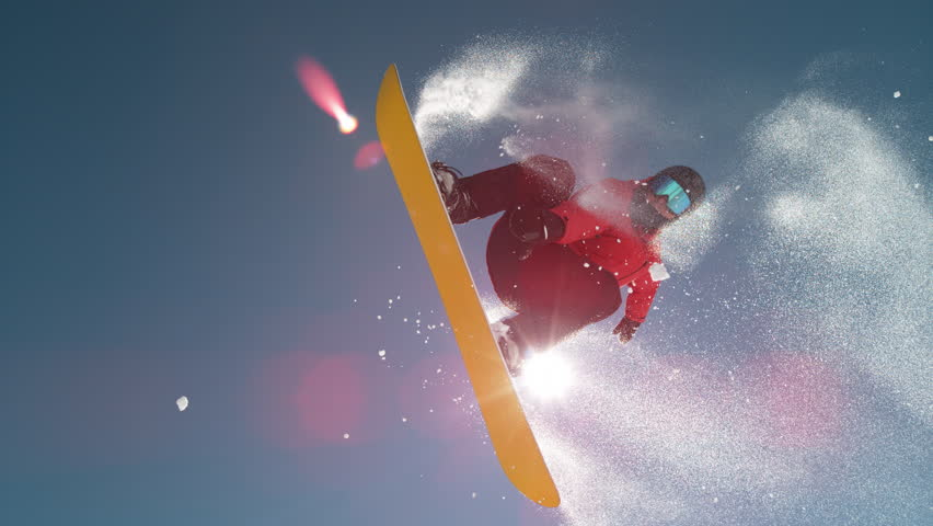 SLOW MOTION CLOSE UP: Snowboarder jumping big air kicker, spraying snowflakes and flying over sun on perfect winter day. Snowboard jump in snow park. Sunbeams shining past jumping boarder in mountains