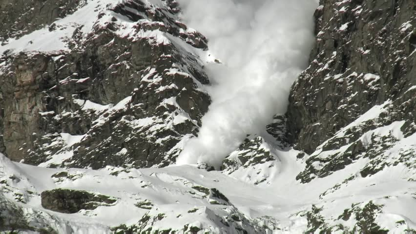 Snow avalanche in the mountains. Alps snow falling from high hills.