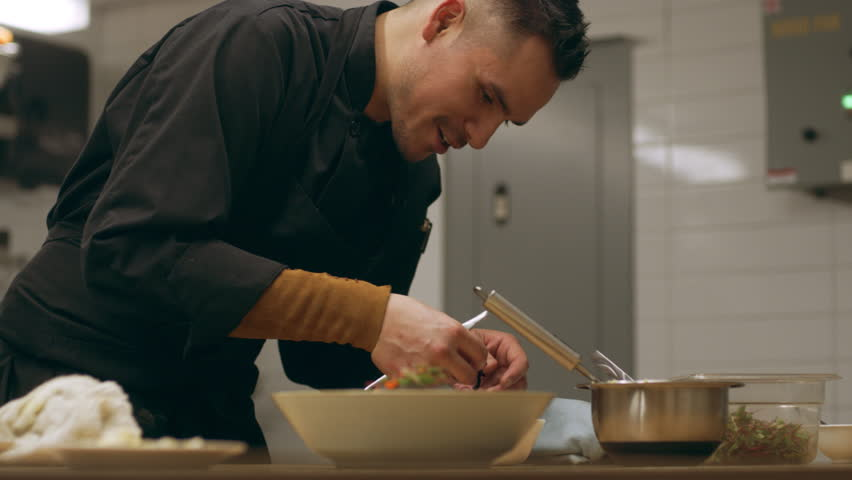 Professional chef finishing plating of sockeye salmon dish in a shallow bowl on a wooden counter in kitchen. Medium close up shot on 4k RED camera.