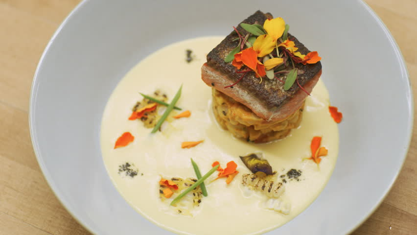 Plating of sockeye salmon dish in a shallow bowl on a wooden counter in kitchen. Close up shot on 4k RED camera.