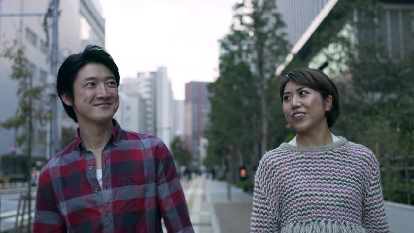 Cheerful happy Japanese couple walking down a quiet metropolitan street. 4k RED camera.