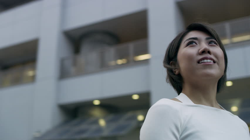 Smiling Japanese woman looking out while standing in a quiet metropolitan city in Japan. Medium close up shot on 4k RED camera on gimbal.