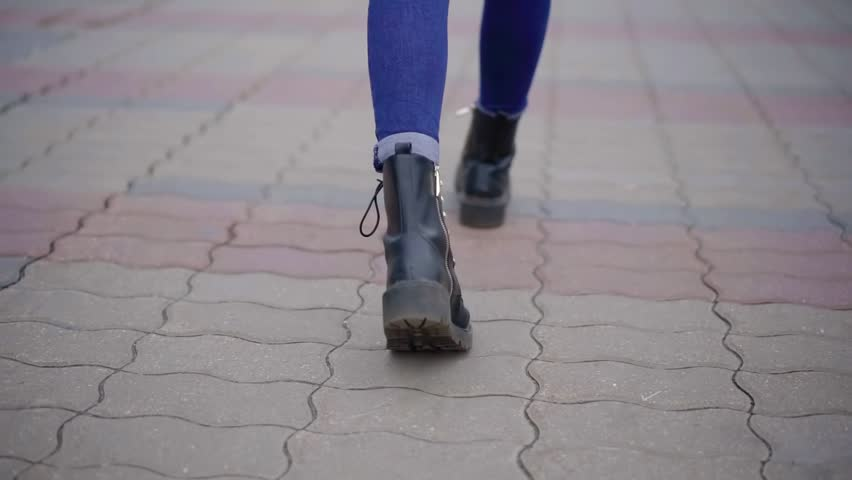 woman is walking in city in daytime in autumn, close-up view of her shoes from back, strolling Royalty-Free Stock Footage #1020290881