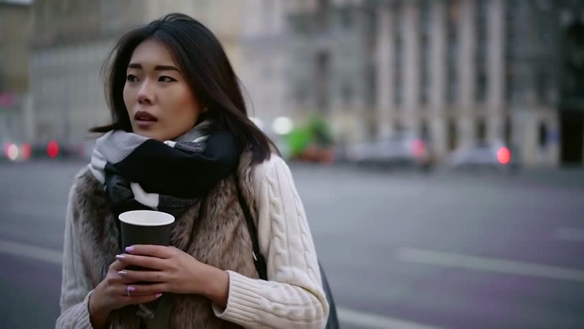 Sad chinese woman is standing alone on city street in cold weather, holding cup of coffee | Shutterstock HD Video #1020290893