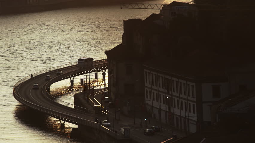 Automobiles on route above river near old buildings at sunset in Porto, Portugal #1020295582