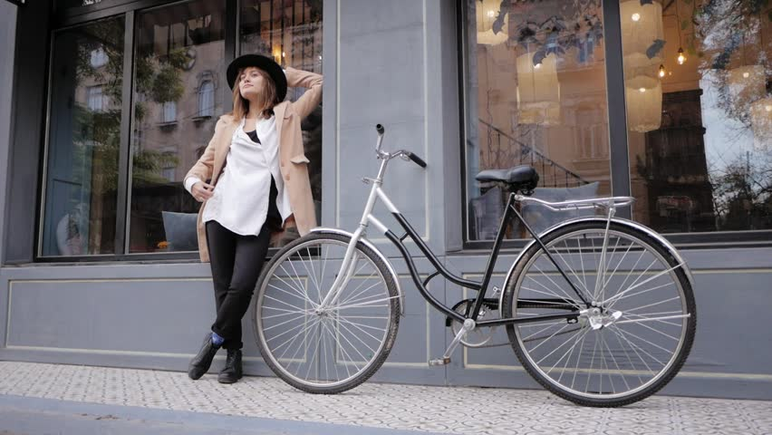 Young woman hipster in hat posing on the street with bicycle | Shutterstock HD Video #1020302830