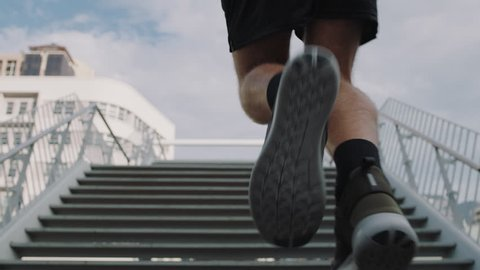 young man runner feet running up stairs training intense cardio workout exercise male athlete legs jogging on steps in urban city background slow motion 4k footage cinematic