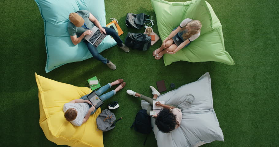 Group of young multi ethnic business students working on business project exam relaxing in vibrant modern recreational workplace above view | Shutterstock HD Video #1020333292