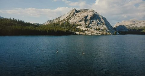 Drone flying above beautiful sunny mountain lake with two kayakers in the center at summer Yosemite national park USA.
