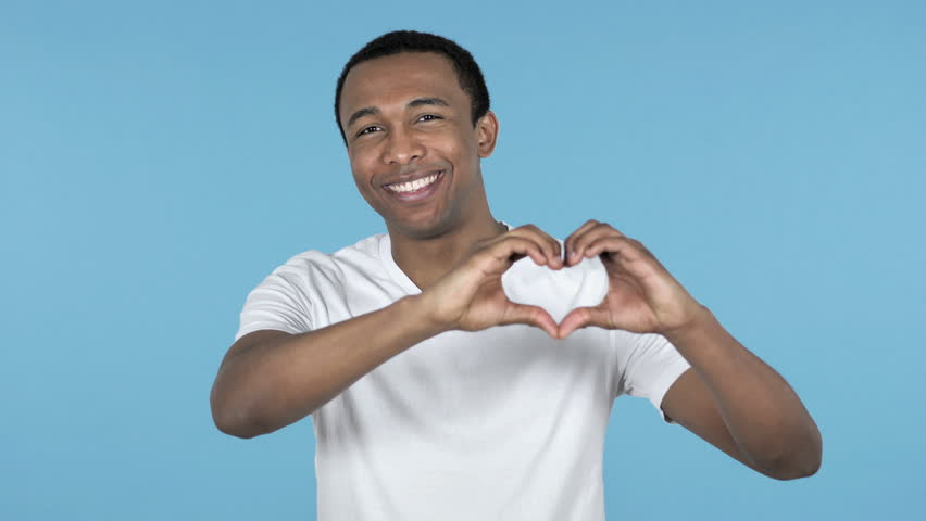 Handmade Heart by Young African Man Isolated on Blue Background | Shutterstock HD Video #1020341635