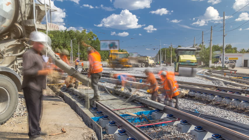 Pouring ready-mixed concrete after placing steel reinforcement to make the road by concrete mixer timelapse. Reconstruction of tram tracks