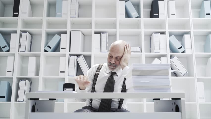 Lazy office worker doing a repetitive dull job, he is stamping a pile of paperwork | Shutterstock HD Video #1020353647