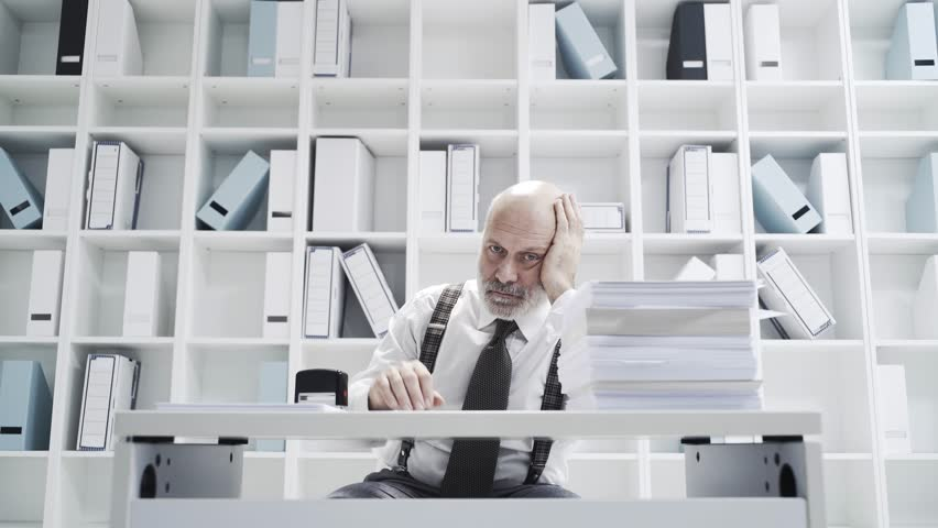 Office worker doing a boring repetitive job like a robot: he is stamping documents and staring at the camera | Shutterstock HD Video #1020353656