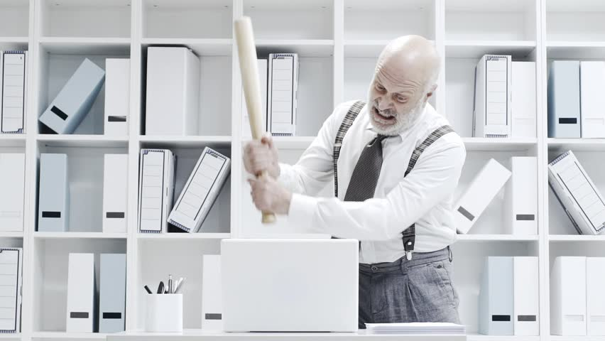 Stressed crazy businessman smashing his laptop in the office using a baseball bat, anger and computer problem concept