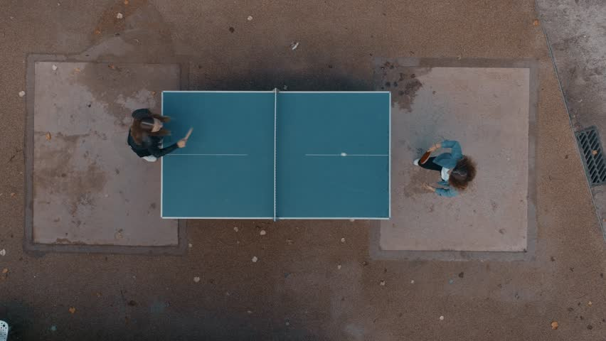 Clean and minimal top drone footage of two best friends or student young girls have fun outdoors. Play ping pong or table tennis in park playground. Laugh and smile in friendly competition game