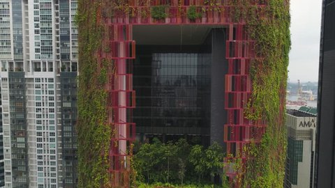 Singapore - 25 September 2018: Bird's eye view of central business district of Singapore and unusual ivy facade hotel. Shot. High density buildings of modern urban cityscape and red walls hotel with