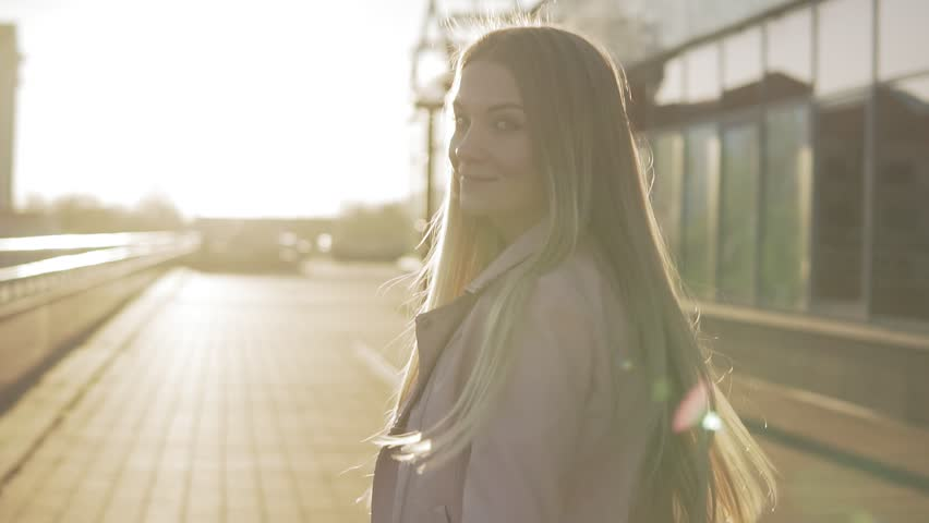 Portrait of pretty caucasian woman with long hair walking in city at sunrise or sunset. Beautiful blonde woman smiling at camera and turning around in slow motion #1020388591
