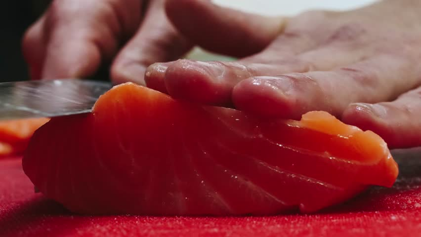 Chef takes out bones from the salmon fillet, cutting fish on slices for cooking sushi in 4k resolution in slow motion | Shutterstock HD Video #1020392323
