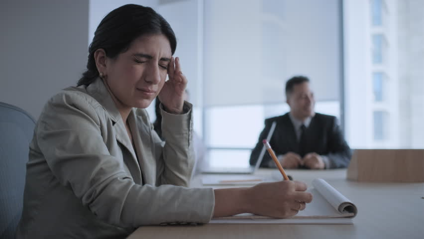 Tired business woman working in office meeting room during conference. Busy latina girl with headache at work. Ill latina businesswoman with flu in corporate room. Health problem, anxiety and pain