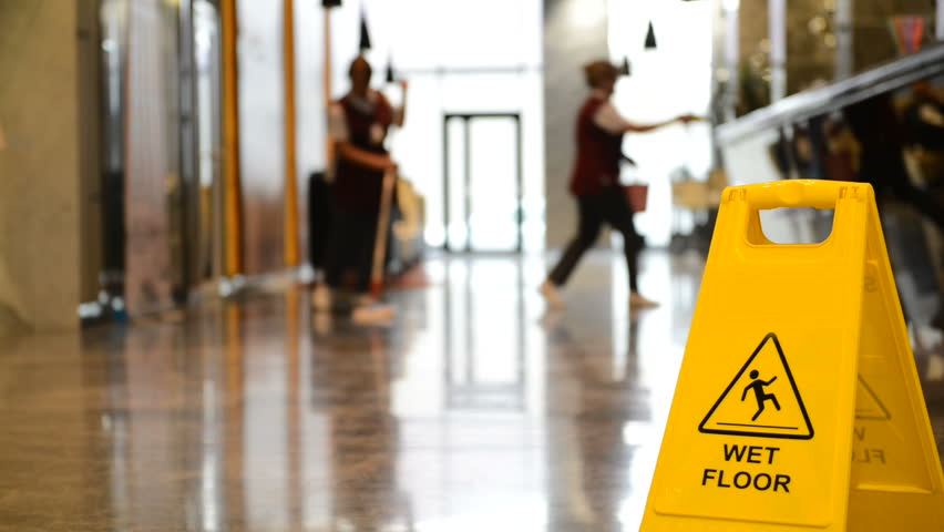Yellow warning sign wet floor. Sign showing warning of caution wet floor and workerw cleaning hall floor of  business building. Royalty-Free Stock Footage #1020412183