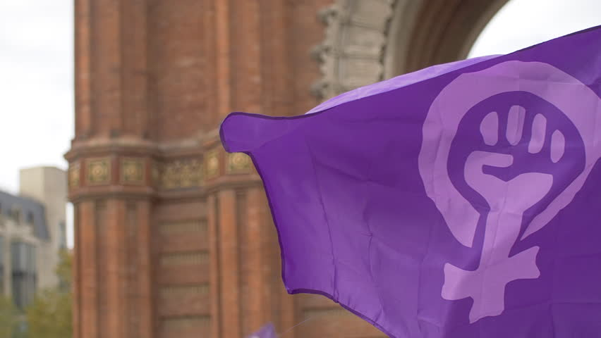 Feminist Flag waving in front of Arc de Triomf in Barcelona. Feminist Activists in a Demonstration. March for the International Day of Nonviolence against Women and Children in Barcelona, Spain. Royalty-Free Stock Footage #1020423043