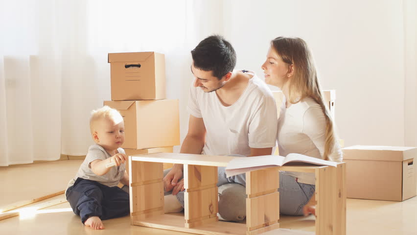 family with little boy reading instruction and assemble furniture together at living room of new apartment pile of moving boxes on background #1020426859