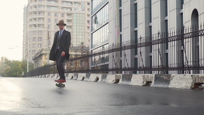 Hipster businessman wear a hat and glasses skateboarding near business office