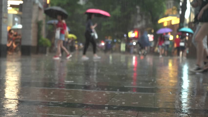 People walking with umbrellas while raining in a commercial street of a big city Royalty-Free Stock Footage #1020434980