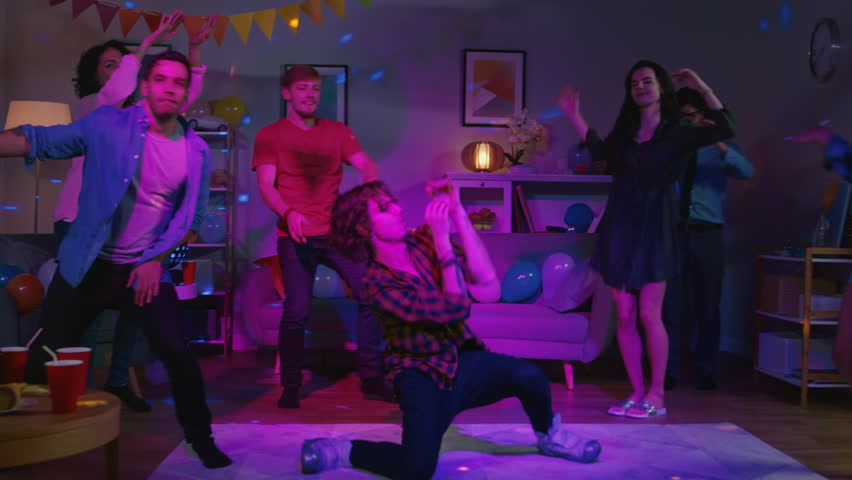 At the College House Party: Diverse Group of Friends Have Fun, Dancing and Socializing. One Guy Does Modern Dance Moves, Girls Cheer. Boys and Girls Dance in the Circle. Disco Neon Strobe Lights. #1020453364