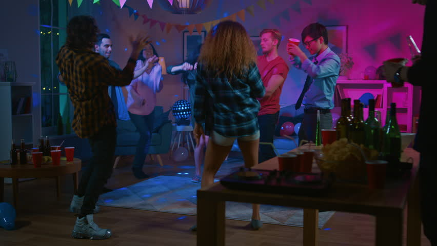 At the College House Party: Diverse Group of Friends Have Fun, Dancing and Socializing. Boys and Girls Dancing in the Circle. Disco Neon Strobe Lights Illuminating Room. Royalty-Free Stock Footage #1020453445
